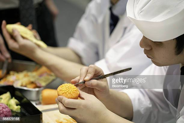An employee carves a garnish vegetable the Japanese art of carving decorative vegetables is known as mukimono during a demonstration at the...