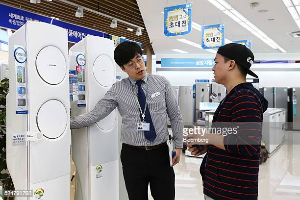 An employee center assists a customer as he looks at Samsung Electronics Co air conditioners at one of the company's digital plaza stores in Seoul...