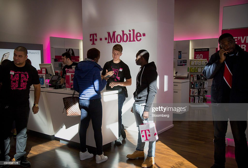 An employee, center, assists customers at a T-Mobile US Inc