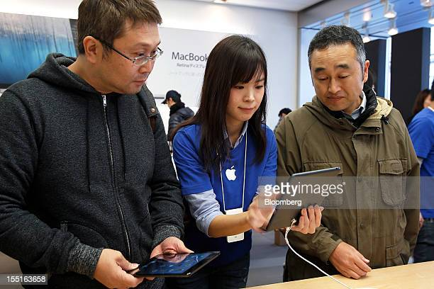 An employee center demonstrates Apple Inc's iPad mini tablet computer for customers at the Apple Store Ginza in Tokyo Japan on Friday Nov 2 2012...