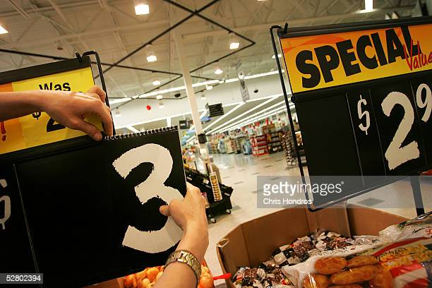 An employee changes a price placard in the grocery section of a WalMart Supercenter May 11 2005 in Troy Ohio WalMart America's largest retailer and...