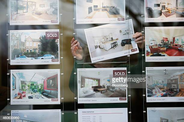 An employee changes a residential property information leaflet displayed in the window of an estate agent in this arranged photograph taken in the...
