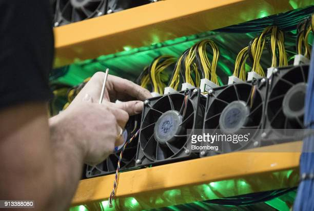 An employee changes the fan on a mining machine at the Bitfarms cryptocurrency farming facility in Farnham Quebec Canada on Wednesday Jan 24 2018...