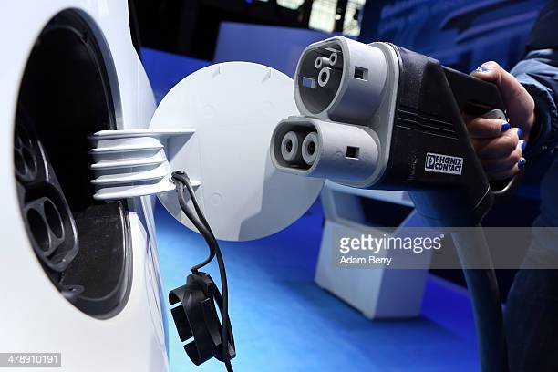 An employee charges a Volkswagen Twin Up! hybrid electric automobile at the Electric Mobility Week , a public Volkswagen event at the former...