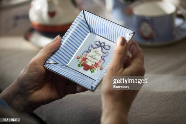 An employee checks a china ashtray made to commemorate the wedding between Henry Windsor and Meghan Markle at Halcyon Days Ltd's factory in...