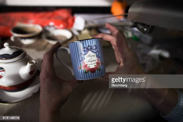 An employee checks a china mug made to commemorate the wedding between Henry Windsor and Meghan Markle at Halcyon Days Ltd's factory in StokeonTrent...