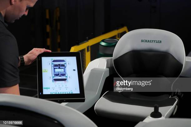 An employee checks a display monitor showing an overview of the inward facing seating as a Schaeffler Mover electric autonomous vehicle undergoes...