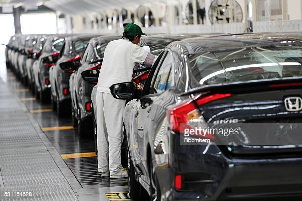 An employee checks a Honda Civic vehicle at the quality control station on the production line of the Honda Motor Co assembly plant in Prachinburi...