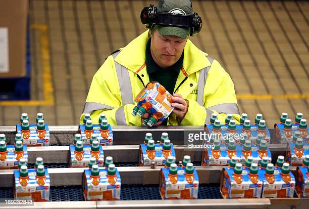 An employee checks a multipack of Robinsons Fruit Shoot tropical drink produced by Britvic Plc as it moves along the production line at the company's...