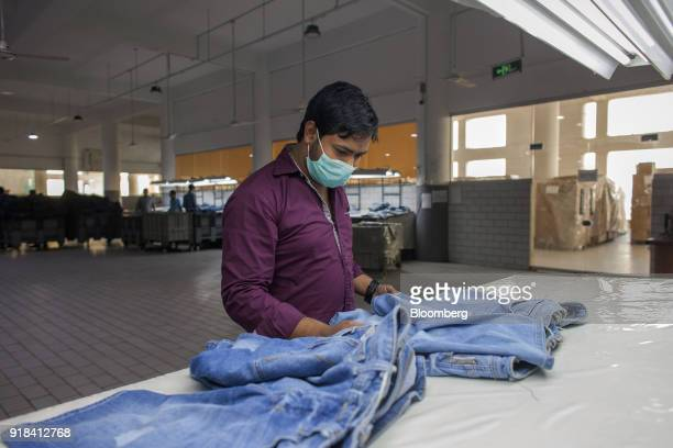An employee checks a pair of jeans inside the washing unit at the Artistic Denim Mills Ltd factory in Karachi Pakistan on Tuesday Feb 6 2018...