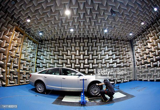 An employee checks a Pirelli C SpA tire during a test in a semianechoic room at the company's research and development facility in Milan Italy on...
