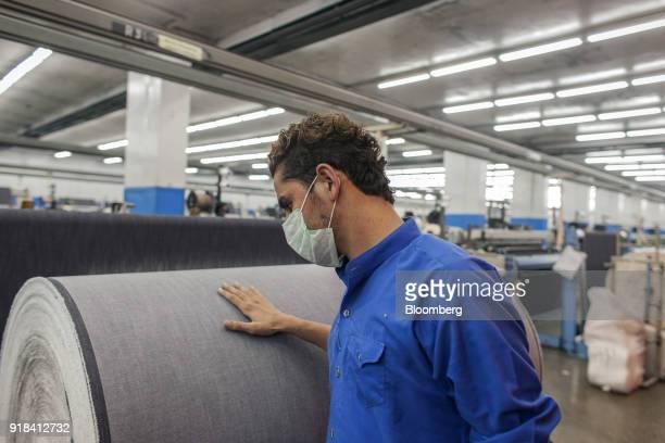 An employee checks a roll of denim fabric in the weaving unit at the Artistic Denim Mills Ltd factory in Karachi Pakistan on Tuesday Feb 6 2018...