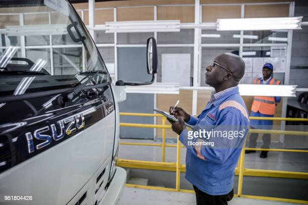 An employee checks an Isuzu NPR NSeries truck on the quality control line inside the Isuzu East Africa Ltd plant in Nairobi Kenya on Thursday April...