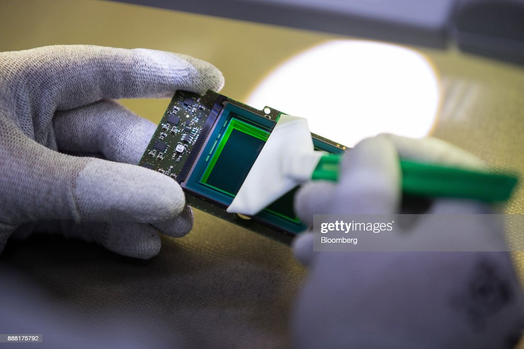 An employee checks and cleans a 24-megapixel sensor during assembly of Leica M10 range-finder digital camera at the Leica Camera AG factory in Wetzlar, Germany, on Tuesday, Nov. 28, 2017. German factory orders unexpectedly rose for a third month in October, in a sign that Europes largest economy will carry its strong momentum into 2018. Photographer: Krisztian Bocsi/Bloomberg via Getty Images