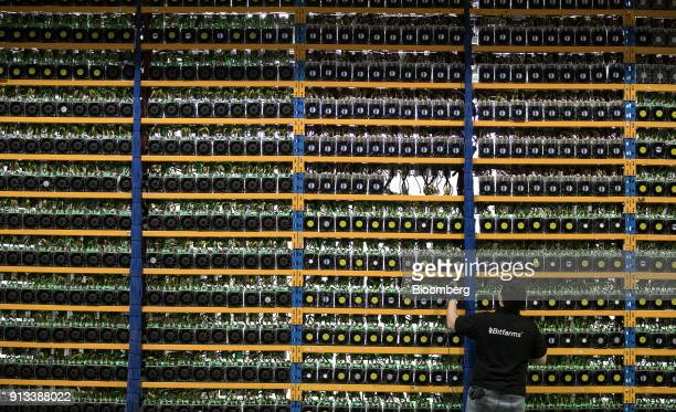An employee checks fans on mining machines at the Bitfarms cryptocurrency farming facility in Farnham Quebec Canada on Wednesday Jan 24 2018 Bitfarms...