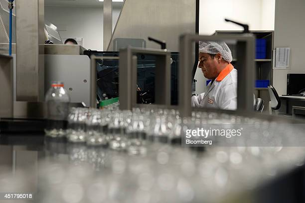 An employee checks glass bottles as they move through an inspection machine prior to being filled with Privigen liquid intravenous immunoglobulin at...