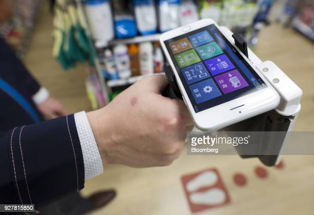 An employee checks items on a shelf with a radiofrequency identification reader operated with a smartphone during a demonstration at a FamilyMart UNY...
