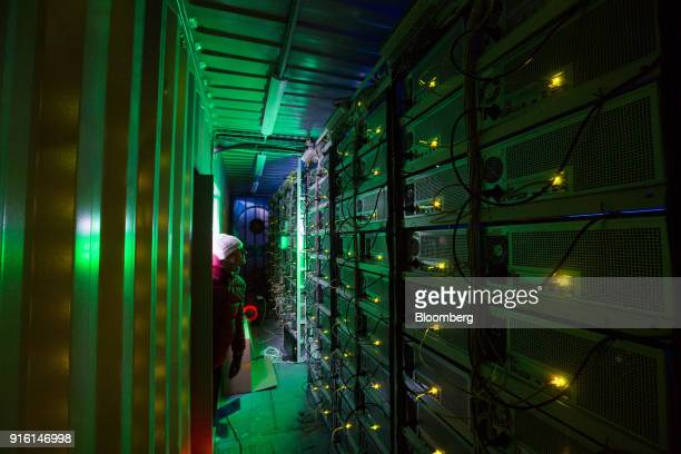 An employee checks on the operation of of cryptocurrency mining rigs operated by BitCluster inside a shipping container converted to a mobile mining...