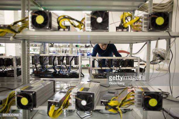 An employee checks power supply units and cooling fans linked to cryptocurrency mining machines at the SberBit mining 'hotel' in Moscow Russia on...