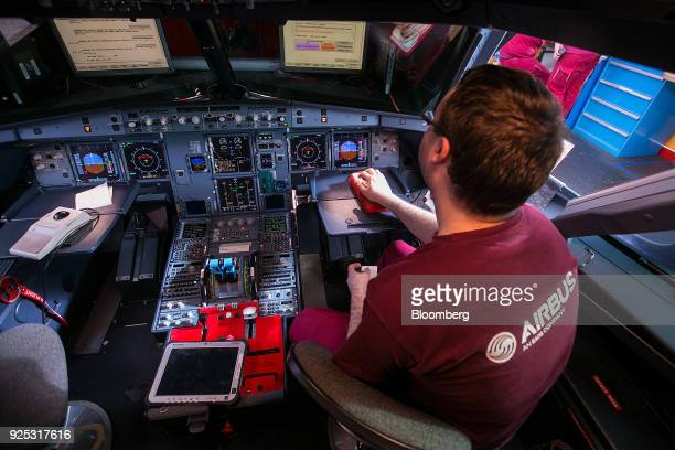 An employee checks software and electrical control systems in the cockpit of an Airbus A321 narrowbody twinengine passenger jet airliner on the...