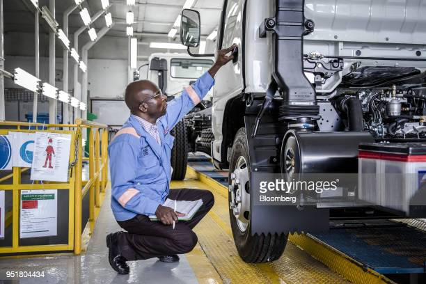 An employee checks the door handle of an Isuzu NPR NSeries truck on the quality control line inside the Isuzu East Africa Ltd plant in Nairobi Kenya...