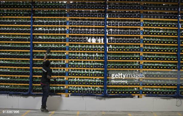 An employee checks the fan on a mining machine at the Bitfarms cryptocurrency farming facility in Farnham, Quebec, Canada, on Wednesday, Jan. 24,...