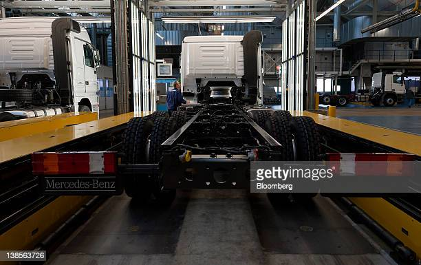 An employee checks the finish on an a truck as it leaves the production line at the MercedesBenz plant in Woerth Germany on Wednesday Feb 8 2012...