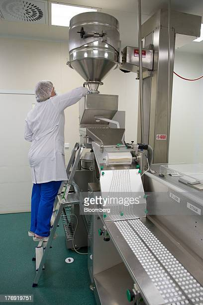 An employee checks the flow of AscophenumP tablets as they move through a packaging machine at OAO Pharmstandard's Leksredstva drug manufacturing...