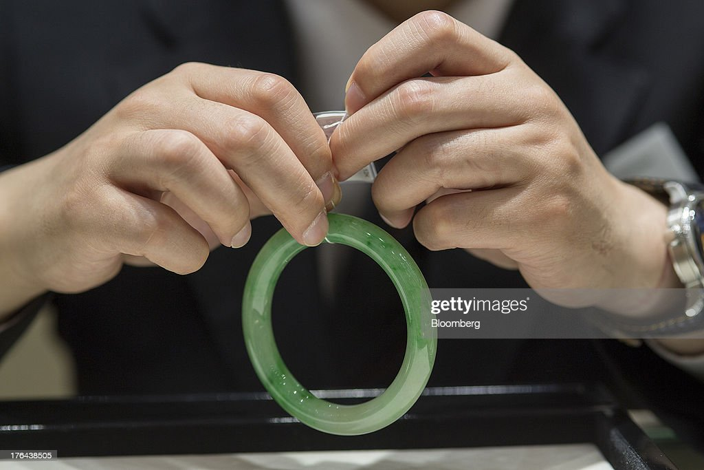 An employee checks the information tag of a jade bangle at a Chow Tai Fook Jewellery Group Ltd. retail store in the Central district of Hong Kong, China, on Tuesday, July 23, 2013. The value of the precious gem is surging with Chinas wealthy snapping up jade necklaces, rings and bracelets as long-term investments. Photographer: Jerome Favre/Bloomberg via Getty Images