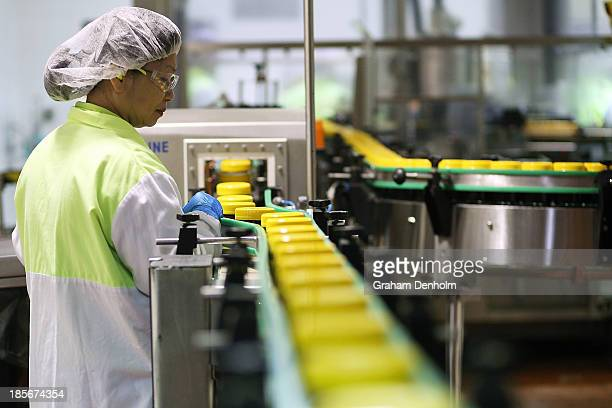 An employee checks the production line during a press call to celebrate the Vegemite brand's 90th year at the Vegemite factory on October 24 2013 in...