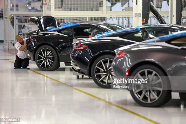 An employee checks the rear of an Aston Martin DB11 luxury automobile in the quality inspection area at Aston Martin Lagonda Ltd's manufacturing and...