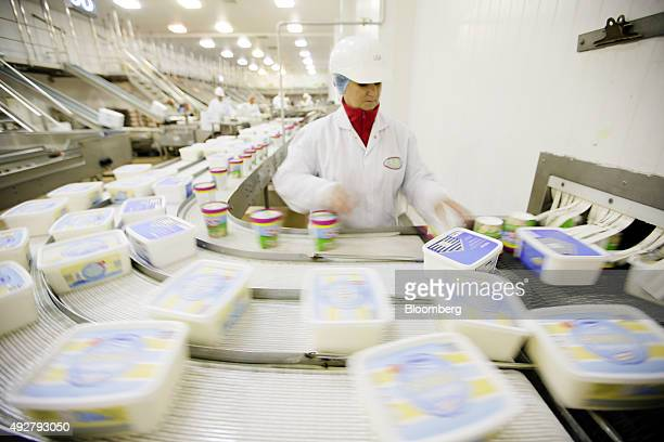 An employee checks tubs of ice cream traveling along the production line at the RR Ice Cream Plc factory in Leeming Bar UK on Wednesday Oct 14 2015...