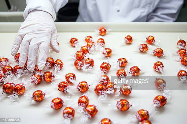 An employee checks wrapped Lindor chocolate balls as they sit on the production line inside the Lindt Spruengli AG factory in Kilchberg Switzerland...