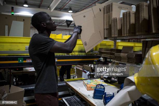 An employee chooses the right size of a box before packing a parcel of merchandise at the Amazoncom MPX5 fulfillment center on November 17 2017 in...