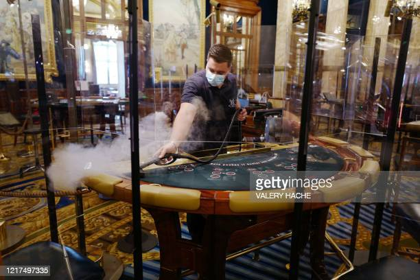 TOPSHOT An employee cleans a blackjack card table before the reopening of the Casino de MonteCarlo property of the Societe des Bains de Mer on June 4...