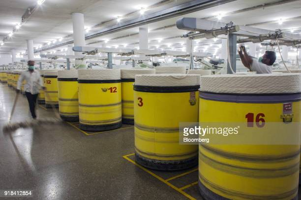 An employee cleans a floor as drawing machinery operates in the spinning unit at the Artistic Denim Mills Ltd factory in Karachi Pakistan on Tuesday...