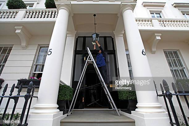 An employee cleans a lamp at the entrance to residential property in the London area of Belgravia in London UK on Thursday Nov 15 2012 London luxury...