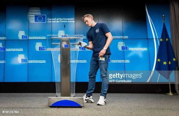 An employee cleans a lectern ahead of a press conference by The High Representative of the European Union for Foreign Affairs and Security Policy and...