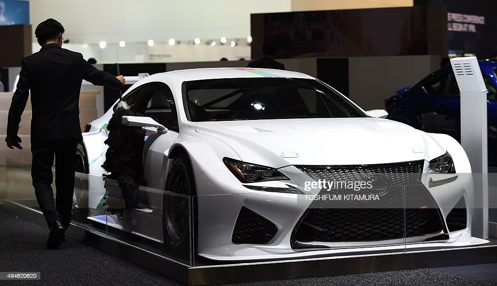 An employee cleans a Lexus RC F GT-3 concept SPEC on display at the ...