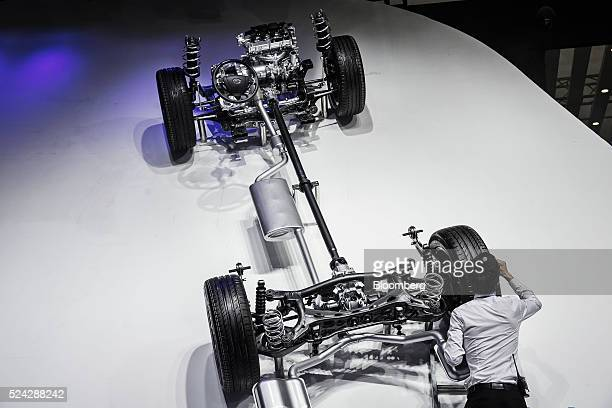 An employee cleans a vehicle chassis display hanging on a wall at the Beijing International Automotive Exhibition in Beijing China on Monday April 25...