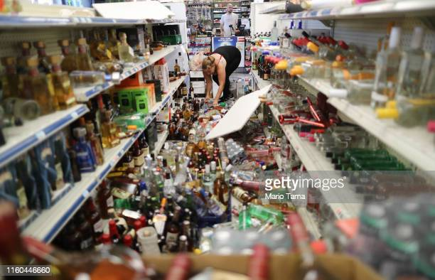 An employee cleans an aisle with toppled bottles scattered on the floor in a convenience store following a 71 magnitude earthquake which struck...