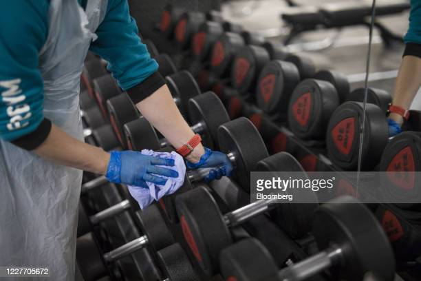 An employee cleans an dumbbell weights at a Pure Gym Group Plc health club, as they prepare for reopening from July 25, in the City of London, U.K.,...