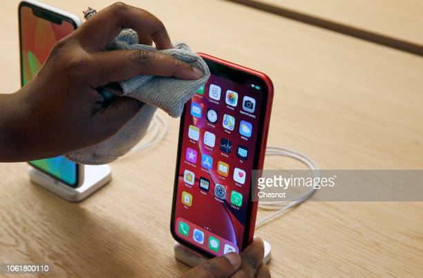 An employee cleans an iPhone Apple XR during the press visit of the new Apple Store ChampsElysees on November 15 2018 in Paris France Apple will open...