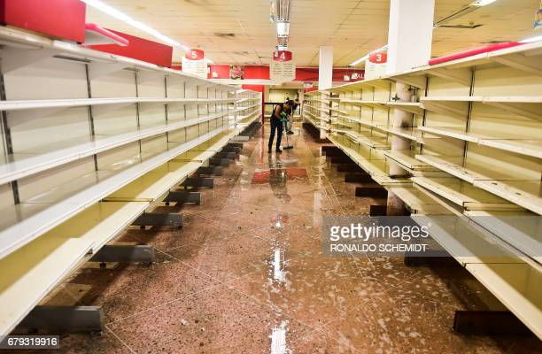 An employee cleans at a supermarket in Valencia Carabobo State on May 5 the day after antigovernment protesters looted stores set fire to cars and...
