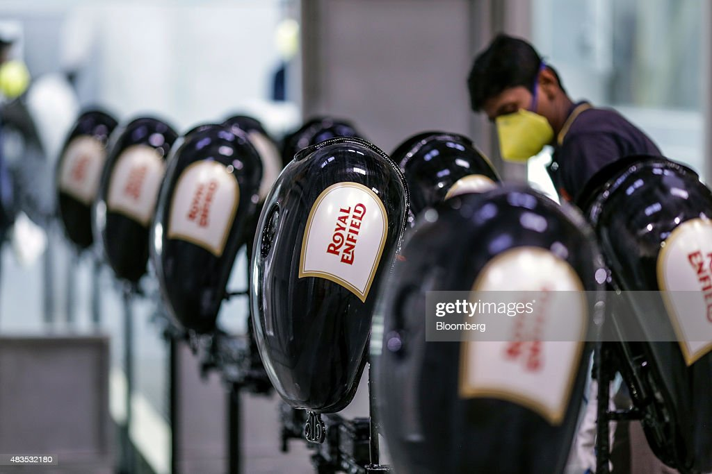 An employee cleans gas tanks for the Royal Enfield Motors Ltd Classic 350 motorcycle moving on a conveyor on the production line at the company`s...