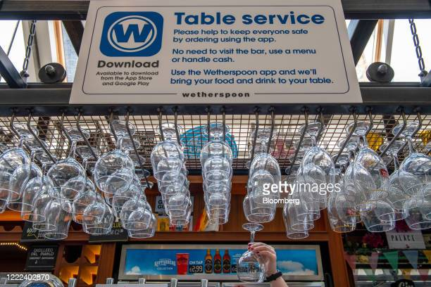 An employee cleans glasses underneath a sign encouraging customers to use an app to order at The Mossy Well pub, operated by J D Wetherspoons Plc, in...