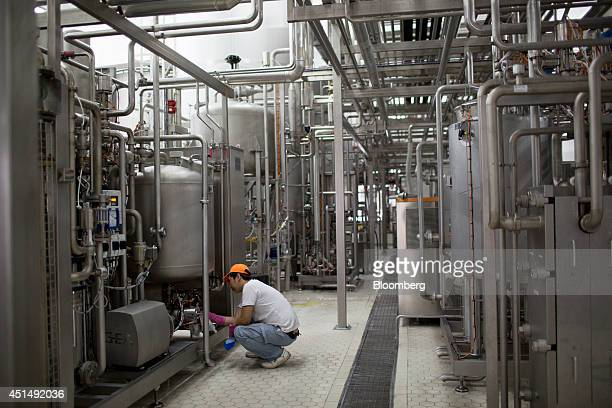 An employee cleans machinery inside the APU JSC dairy plant in Ulaanbaatar Mongolia on Tuesday June 24 2014 APU is Mongolia's largest spirit and...