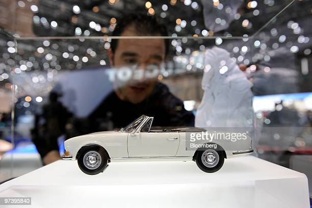 An employee cleans the display case of a model of a 1968 Peugeot 504 automobile on display on the second press day of the Geneva International Motor...