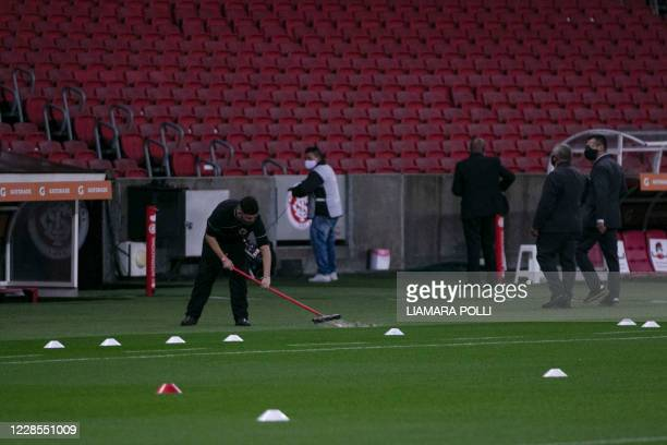 An employee cleans the field before a closed-door Copa Libertadores group phase football match between Brazil's Internacional and Colombia's America...