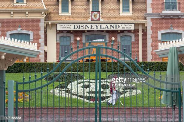 An employee cleans the grounds behind the closed gates of Disneyland Park on the first day of the closure of Disneyland and Disney California...